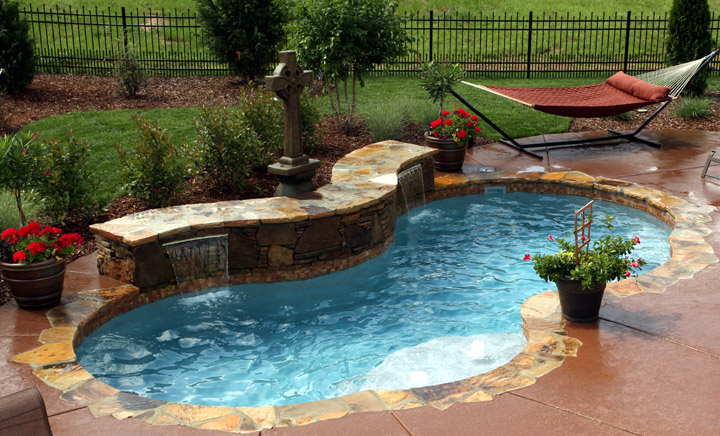 Fiberglass pool with stone waterfall feature